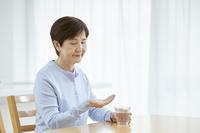 薬を飲むシニア日本人女性