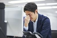 目頭を押さえる日本人ビジネスマン