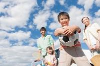 青空の下に立つ笑顔の日本人家族