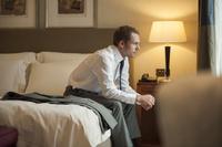 ホテルのベッドに座るビジネスマン