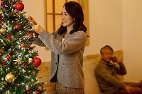 クリスマスツリーを飾る日本人シニア夫婦