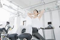 フィットネスジムのマシーンを使って腹筋をする日本人女性