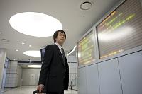 電光掲示板の前のビジネスマン