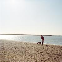 砂浜を歩く外国人女性と犬
