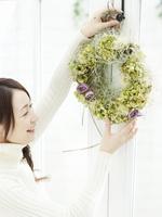 グリーンのリースを飾る日本人女性