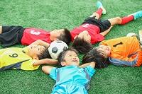 寝そべるサッカー少年