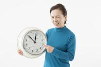 時計を指して苦い顔をするシニアの日本人女性