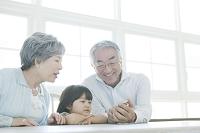 孫娘と携帯電をを見るシニア夫婦