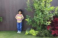 茶色い塀の前に立つ少年