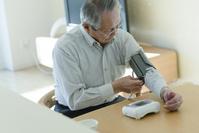 血圧を測るシニアの日本人男性