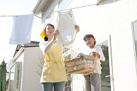 洗濯物を干す女性と手伝う女の子