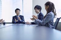 会議で拍手をする日本人ビジネスパーソン