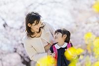 菜の花と桜の咲く公園で母親と遊ぶランドセル姿の新一年生