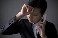 電話をしながら悩む男性