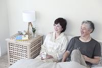 ベッドで微笑むミドルカップル