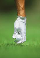 ゴルフボールをセットするゴルファーの手