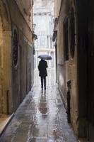 雨の路地で傘をさす男性