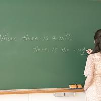 黒板に文字を書く女子大生