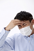 発熱で頭に手をやるマスクをした日本人男性