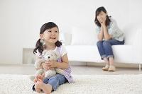 テディベアとリビングでくつろぐお母さんと女の子