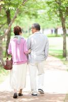 公園を歩く日本人シニア夫婦