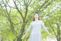 手を伸ばして目を閉じる日本人女性
