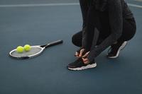 テニスシューズの紐を結ぶ女性