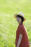 草原で微笑む帽子をかぶった若い女性