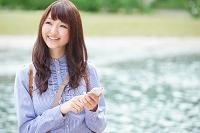 水辺で携帯を操作する日本人女性