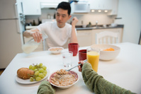 キッチンテーブルで朝食を食べるカップル