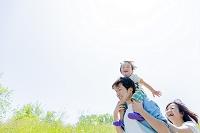 公園を歩く息子と両親