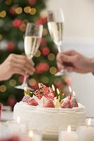 クリスマスケーキとシャンパンで乾杯する手