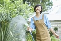 庭で水を撒く中年女性
