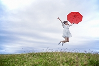 草原で傘を持ってジャンプする日本人女性