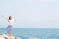 海辺に立って大きく手を広げる日本人女性