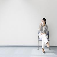 壁際の椅子に座るビジネスウーマン