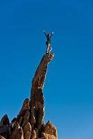 岩山の先端で両手を上げる外国人女性