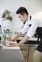 コンピューターを使うカフェのオーナー