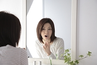 鏡を見て歯磨きする日本人女性