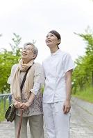 笑顔で空を見上げる女性介護士とシニア女性