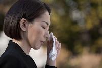 ハンカチで涙を拭う喪服姿の日本人女性の横顔