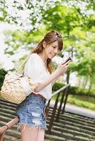 新緑と携帯を持つ日本人女性
