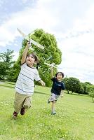 公園で模型飛行機を飛ばす日本人の子供たち