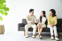 リビングルームのソファに座ってPCを見る家族