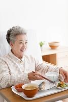 介護ベッドで食事をするシニア女性