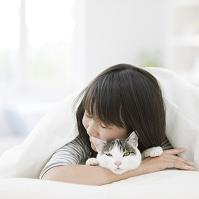 猫を抱いて寝る女性