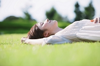 芝生の上でくつろぐ日本人女性