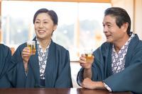 ビールで乾杯す浴衣と羽織の中高年夫婦