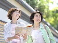 地図を持ち遠くを見る母と娘