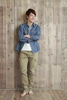 木の壁の前で微笑む若い男性